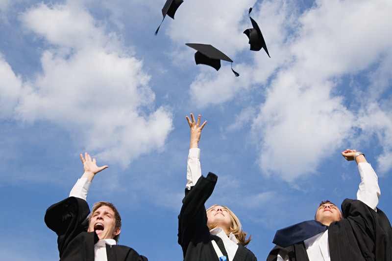 High school graduates throwing their mortarboards in the air